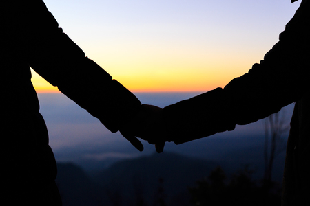 Couple holding by hands on beautiful sunset Stock Photo