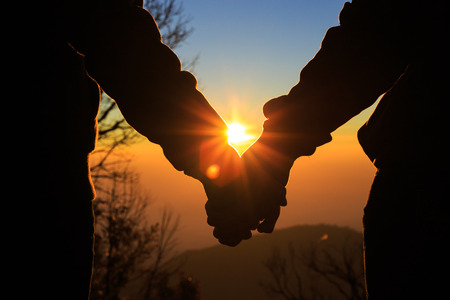 Couple holding by hands on beautiful sunset 免版税图像