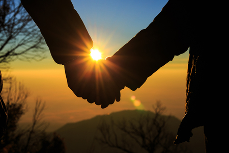 Couple holding by hands on beautiful sunset 스톡 콘텐츠