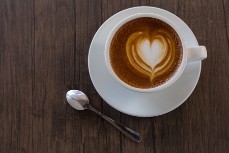 close up cup of coffee with heart pattern in a white cup on wooden background,latte art Stock Photo