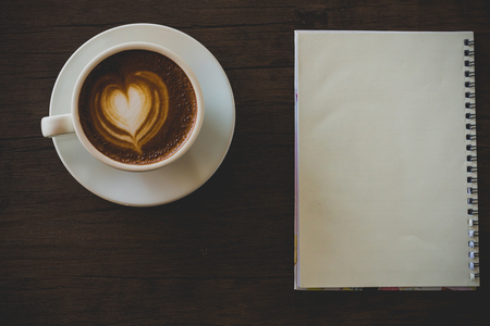 Blank notebook on the coffee table, latte art Stock Photo - 99382316