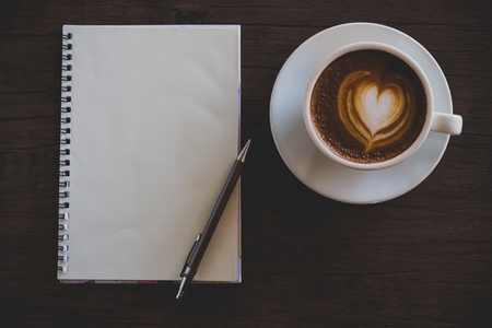 Blank notebook on the coffee table, latte art