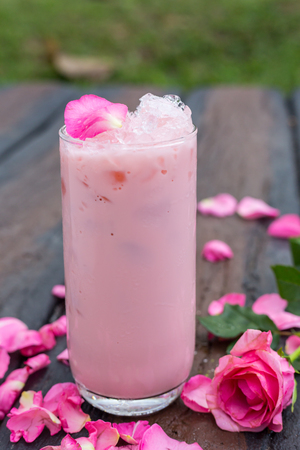 Ice tea with rose milk on wooden table