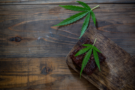 marijuana leaf on a marijuana brownie on wooden table