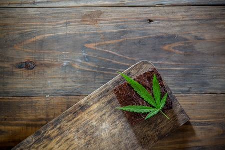 marijuana leaf on a marijuana brownie on wooden table