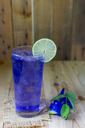 Butterfly pea juice with ice in transparent cup serve on wooden table with flower.