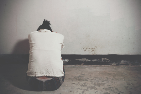 Desaturated grunge image of a very sad adult woman crying