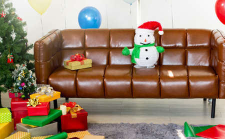 Snowman on the sofa with a gift box and Christmas tree Foto de archivo