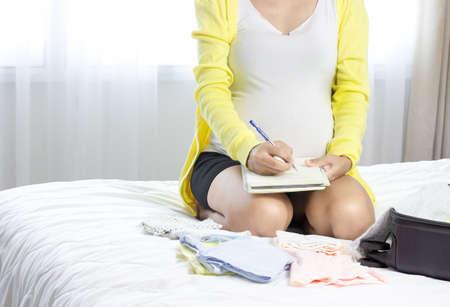 Pregnant woman writing packing list for maternity hospital Standard-Bild