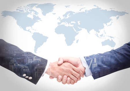 Business people shake hands with a map in the background,Agreement, cooperation,Closeup