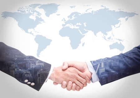 Geschäftsleute schütteln sich die Hände mit einer Karte im Hintergrund, Vereinbarung, Zusammenarbeit, Nahaufnahme