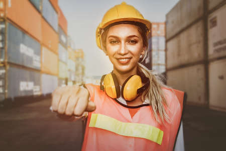 Portrait European female workers wear earloop, reduce noise and yellow helmet, work in the field, warehouse and container, readiness and happiness in work 版權商用圖片