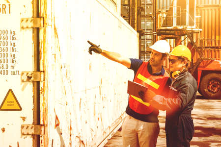 Team work in the engineering industry controls the maintenance of damaged and rusty containers for correction by pointing to the damage point and taking notes by assistants. 版權商用圖片