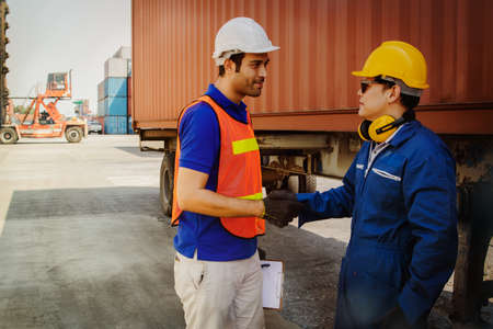 Shaking hands teamwork of industrial technicians working in the establishment, container, friendship between a variety of races, among which effective collaboration.