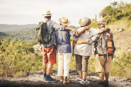 Group of elderly seniors traveling nature, forests and mountains standing with their backs embracing each other with joy, love, and happiness when traveling together with purpose.