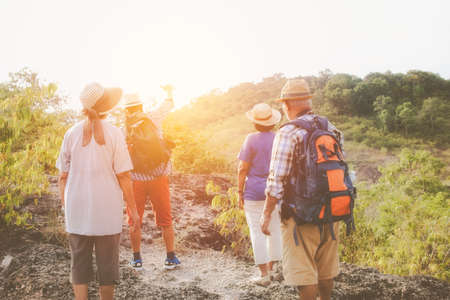 Group of four retired senior friends walk together as a team, travel adventures, carry a backpack behind, study nature and mountains with physical, healthy bodies, watch the sunset.