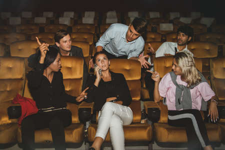 Young woman talking on the phone among moviegoers so annoying others that men and others who sit next to each other admonish her because she is not happy with her manners.