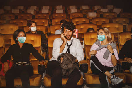 Man talking on the phone and not wearing a virus mask The global epidemic virus in the middle of a crowd of moviegoers wearing masks and annoying others and sit unspaced