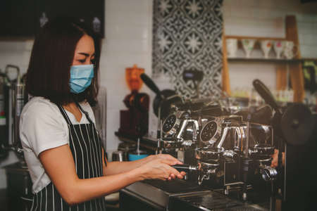 Asian female barista wearing a mask makes coffee at the counter : Selective Focus