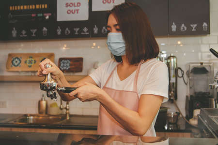 Businesswoman, Asian Barista wearing a mask, is holding a port filter coffee filter grind quality Arabica coffee beans to brew the best and delicious coffee to serve customers : Selective Focus