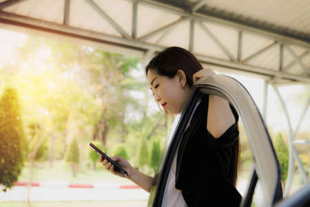Concept of everyday life, the online social world : Beautiful woman uses a smartphone anywhere, even her free time, always using the phone even in the parking lot : Copy space
