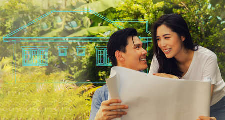 Happy Asian couple admires the blueprints of the beautifully designed houses. There is excitement, satisfaction and delight in getting a new home built on their land.