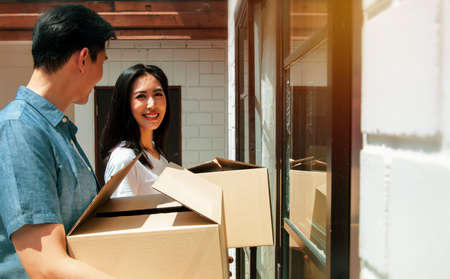 Young couples planning their families, moving into a new home,family happiness and living together : Asian couple brings home accessories boxes to the door of their family's new home with happy smile Standard-Bild