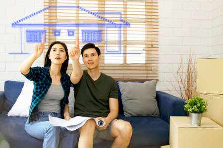 Happy Asian couple admires the blueprints of the beautifully designed houses. There is excitement, satisfaction and delight in getting a new home built on their land. Standard-Bild