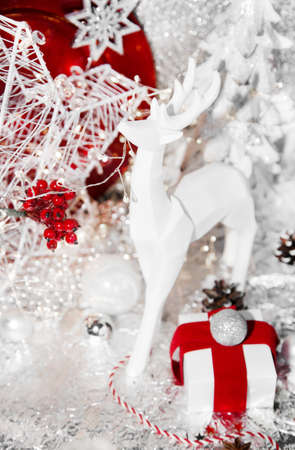 Christmas red, xmas white reindeer, red plate, gift, red ribbon, mountain ash, rowan, christmas tree and balls, on white background, with sweets, cinnamon, winter cone and lights Foto de archivo