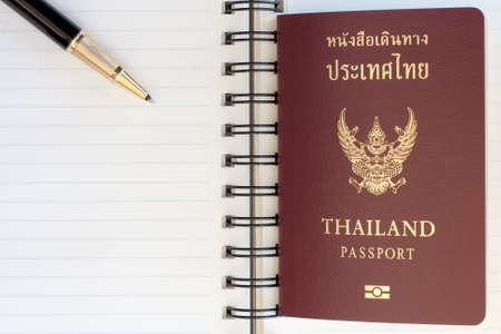 Thailand passport and pen on blank page in a spiral bound notebook photo
