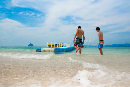 Two men are relaxing on holiday on the beach in Phuket Thailand photo