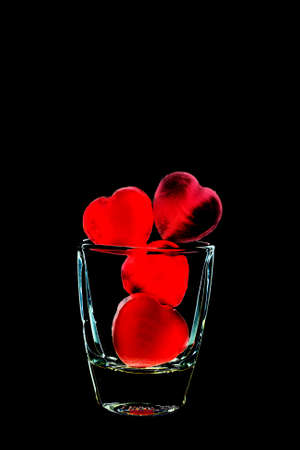 ceramicist: Creation of red heart-shaped candies in glass isolated on black background