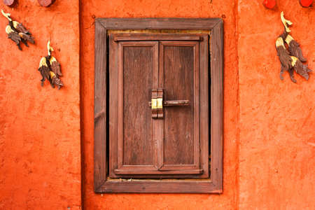 Grunge Wood window on orange cement wall photo