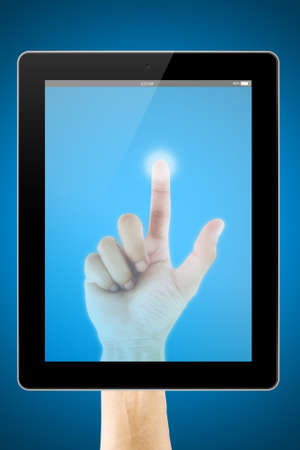 Finger touching screen on tablet computer photo