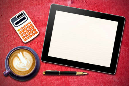 Touch screen device and stationery with cup of coffee on  Grunge Red wooden  background photo