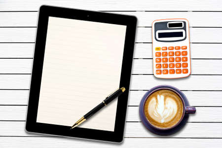 Touch screen device and stationery with cup of coffee on  white wood panel background photo