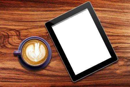 木材のテーブルにコーヒーのカップとのタブレット コンピューター