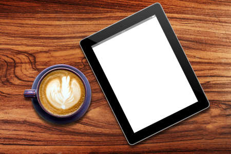 Tablet computer on Wood Table with a cup of coffee photo