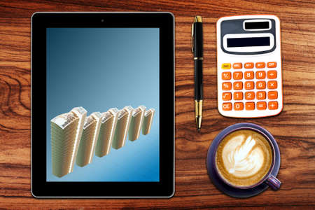 Tablet PC with business money growth graph,stationery  and cup of coffee on  Grunge  wooden background photo
