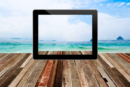 Tablet computer on texture of perspective  wood floor in a room interior  with beautiful sea and sky background  photo