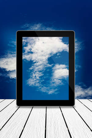 Tablet computer on wood,cloudy sky computing technology concept Stock Photo