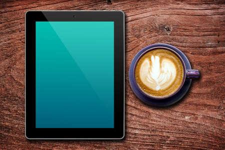 空白のタブレットと木製の背景の上にコーヒーを 1 杯