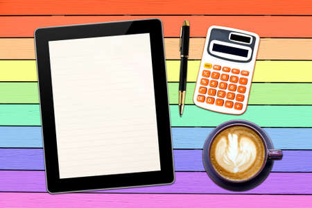 Blank line Touch screen device and stationery with cup of coffee on  colorful wood panel background photo
