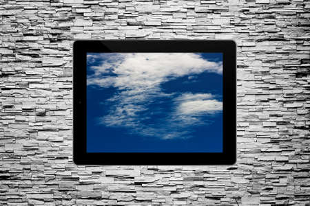 Cloudy sky painting in tablet computer on grunge brick wall Stock Photo - 15423936