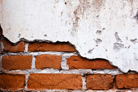 old brick wall with cracked stucco layer background photo