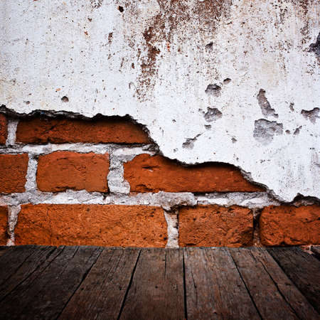 Wood floor with grunge brick wall photo