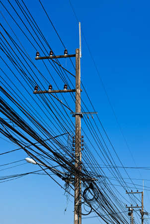 Energy and technology: electrical post by the road with power line cables, transformers and phone lines against bright blue sky  photo