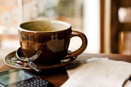 カップと木製テーブル カフェでスマート フォン 写真素材