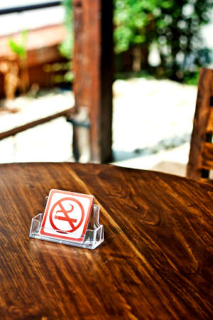 No smoking sign on wood table in cafe.