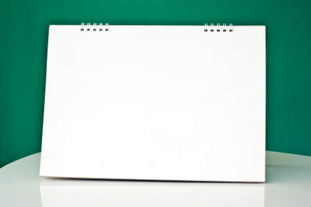 Blank desktop calendar on the table in the office green background photo